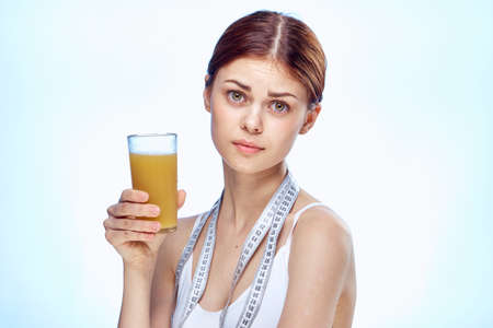 Beautiful young woman on a white-blue background holds a glass of juice.