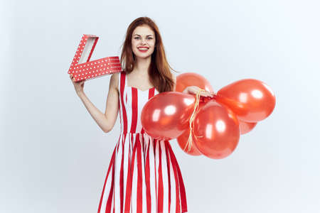 woman holds a red box and balls, smile, gifts.