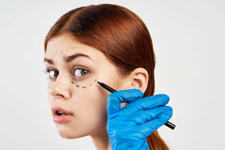 girl in latex glove makes notes on her face.