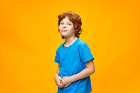 Photo pour A frustrated red-haired boy touches his stomach with his hands - image libre de droit
