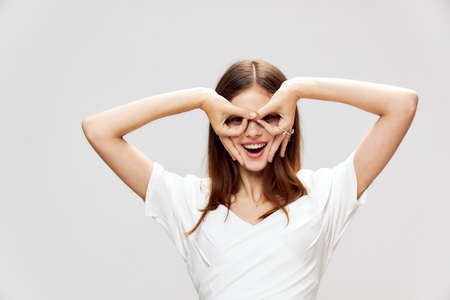 Woman holds her hands in front of her face in the form of a mask smile white dress emotions