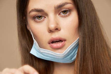 Photo pour Woman with medical mask on ears open mouth model close-up - image libre de droit