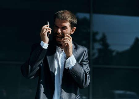 Photo pour Business man communicates on the phone outdoors emotions executive manager lifestyle - image libre de droit