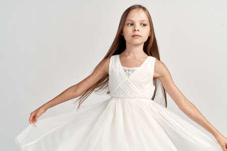 Photo pour girl ballerina in white costume pointe shoes tutu dance light background cropped view - image libre de droit