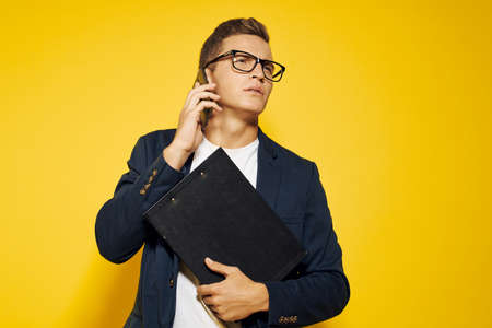 Photo pour business man at work wearing glasses and a jacket on a yellow background talking on the phone employee model - image libre de droit