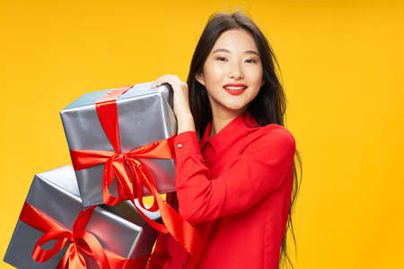 Photo for Woman with gifts Asian appearance red shirt holiday birthday - Royalty Free Image
