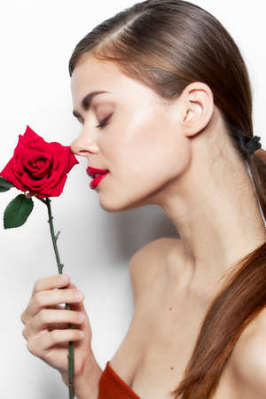 Photo for Woman with flower Sniffing red lips closed eyes bright makeup - Royalty Free Image