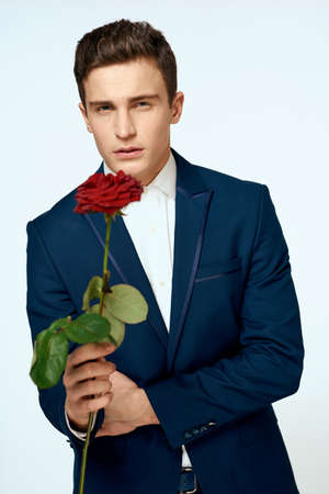 Photo pour A man in a suit with a rose in his hands a gift date light background - image libre de droit
