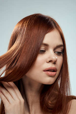 Photo pour pretty redhead woman holding her hair with hands grooming naked shoulders light background - image libre de droit