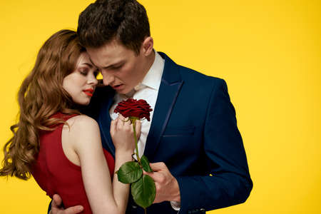 Photo pour A romantic man hugs a woman in a red dress with a rose in his hand on a yellow background - image libre de droit