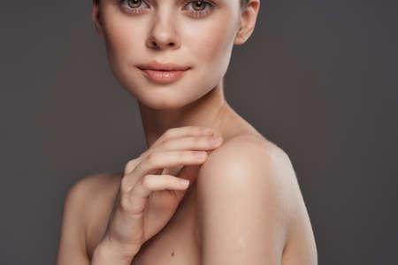 Photo pour Beautiful woman naked shoulders cosmetics clean skin charm gray background studio - image libre de droit