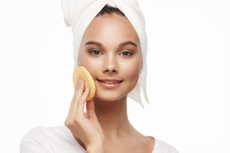 Photo pour Clean skin of the face soft sponge charming girl with a towel - image libre de droit