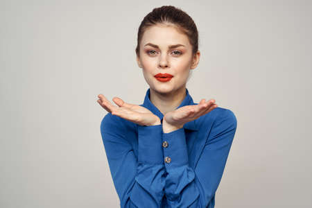 Photo for Portrait of a beautiful woman with red lips on a light background and a blue shirt cropped view - Royalty Free Image