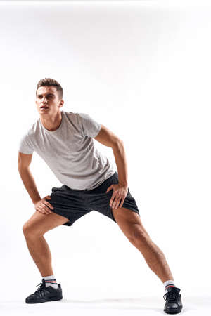 Foto per A sports man in shorts and a full-length T-shirt does exercises on a light background - Immagine Royalty Free