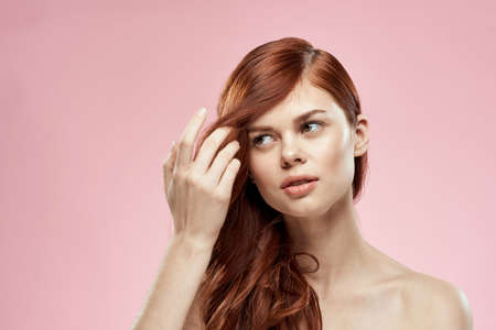 Photo for woman holding hair with hand problems hairstyle care emotions bare shoulders pink background - Royalty Free Image