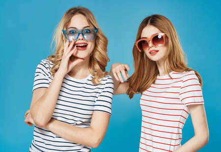 Photo pour cheerful women wearing sunglasses with blue background. - image libre de droit