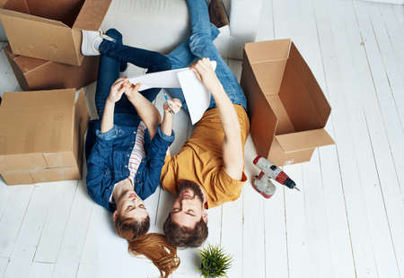 Photo pour A man and a woman with boxes are moving. Well, an apartment is being renovated by a family - image libre de droit