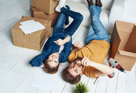 Photo pour Men and women lie on the floor indoors with boxes of documents of flowers in a pot moving - image libre de droit