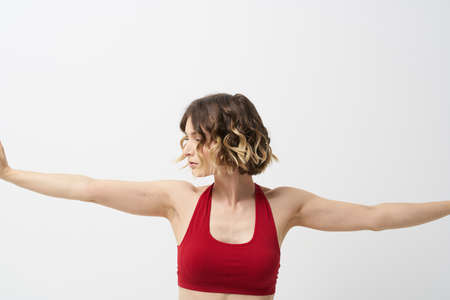 Photo pour the girl is engaged in yoga on a light background Red T-shirt gesticulating with his hands - image libre de droit