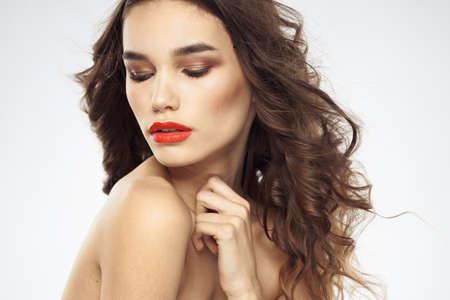 Foto de Beautiful woman with drawn swords bright makeup glamor close-up light background - Imagen libre de derechos
