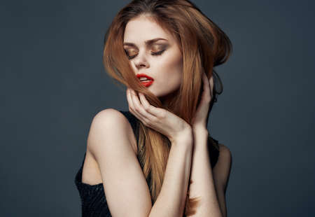 Photo pour red-haired lady in a black dress with red lips and eye shadow - image libre de droit