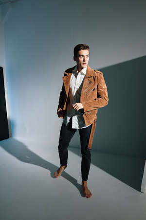 Photo pour A guy in a brown coat and jeans stands barefoot on the floor, top view - image libre de droit