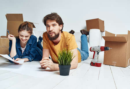 Photo for Moving to an apartment a man and a woman lie on the floor and a flower in a pot - Royalty Free Image