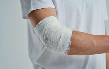 man with bandaged arm elbow and finger injury medicine