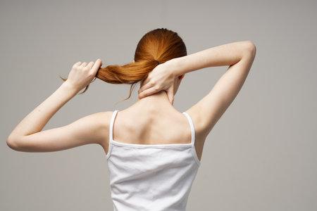 Photo pour woman t-shirt touches her back with hands back view - image libre de droit