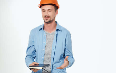 Photo pour male architect in orange hard hat working gray background cropped view - image libre de droit