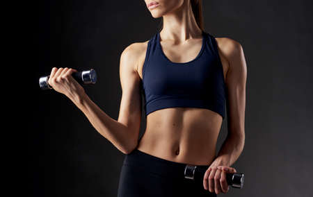 Photo pour woman with pumped up abdominal muscles holds a dumbbell in her hand on a dark background - image libre de droit