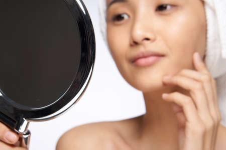 Foto de pretty woman looking in the mirror healthy skin rejuvenation spa treatments - Imagen libre de derechos
