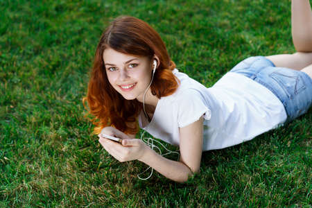 Photo for woman lies on the lawn with a phone in her hands relaxing in the park - Royalty Free Image