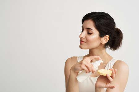 Photo pour woman in white t-shirt Sponge with cream clean skin health cosmetics - image libre de droit