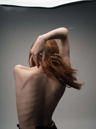 Photo pour Nude red-haired woman touching herself with hands cropped back view - image libre de droit