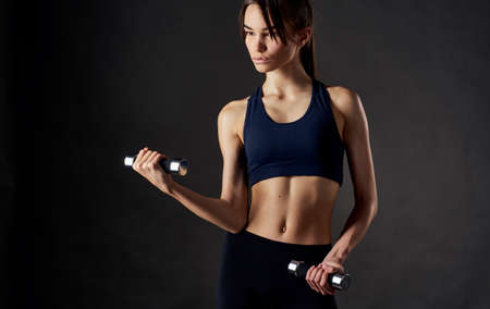 Photo for woman with muscles doing sports dumbbells in her hands and slim figure - Royalty Free Image