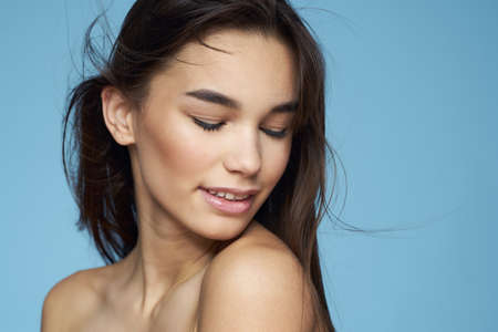 Photo for pretty brunette naked shoulders long hair skin care blue background - Royalty Free Image