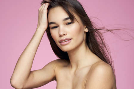 Photo pour Brunette with bare shoulders holding her hair clean skin pink background - image libre de droit