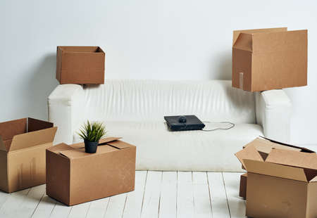 Photo for Boxes with things white sofa unpacking office moving - Royalty Free Image