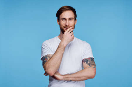 Photo pour Cheerful man in white t-shirt tattoo on his arms cropped view fashion - image libre de droit