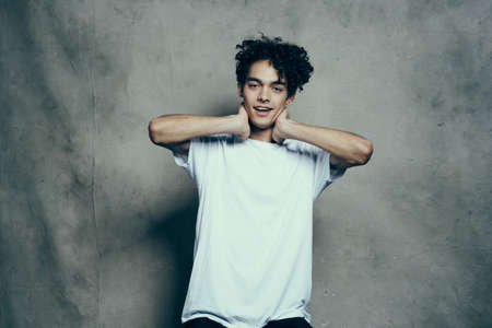 Photo pour Cheerful guy with curly hair gestures with his hands near his face on a gray fabric background in a white t-shirt - image libre de droit