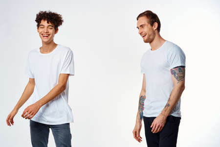 Photo pour Two cheerful friends in white T-shirts joy Positive light background - image libre de droit