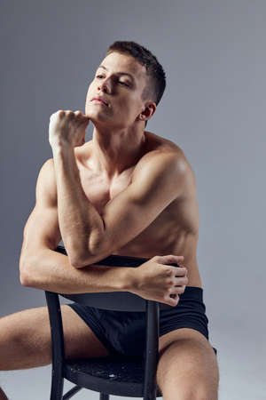 Photo pour a handsome man with a pumped-up body sits with his elbows on the back of a chair - image libre de droit