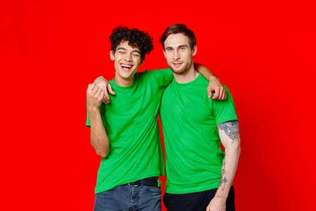 Photo pour Two man green t-shirts embrace emotions friendship red background - image libre de droit