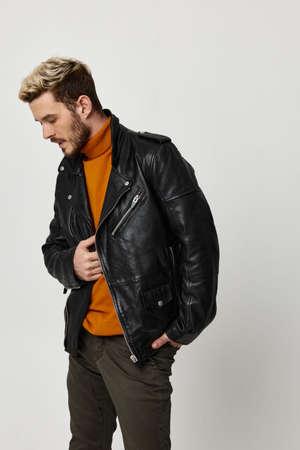 Photo pour upset man in a leather jacket touches his waist on a light background - image libre de droit