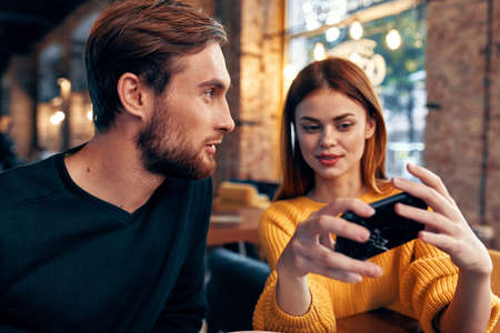 Photo pour a woman in a sweater with a mobile phone and a guy with a beard are sitting in a restaurant - image libre de droit