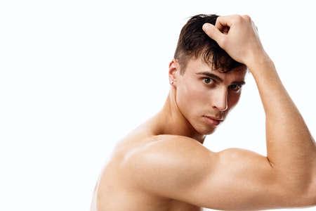 Photo pour confident man athlete with a pumped-up torso touches his head with his hand - image libre de droit