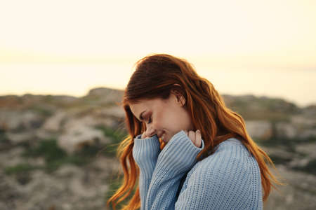 Photo for cheerful woman in a blue sweater outdoors sunset travel vacation - Royalty Free Image