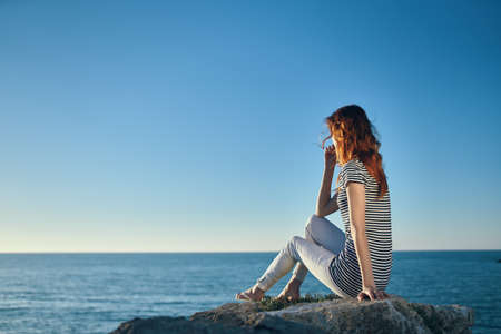 Photo for Woman hiker on a rock near the sea sunset blue sky and transparent water model - Royalty Free Image