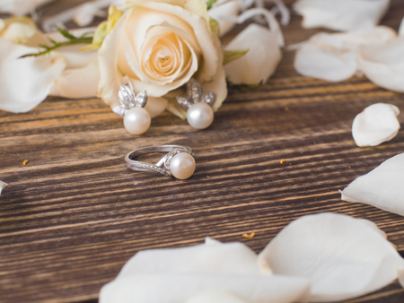 Pearl ring and earrings with white rose on dark wooden background, close up